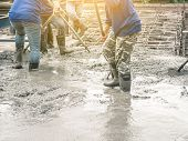 Workers using a wooden spatula for cement after Pouring ready-mixed concrete on steel reinforcement to make the road by mixing mobile the concrete mixer. poster