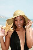a beautiful young african american woman wears a sun hat and shows off a starfish she found poster
