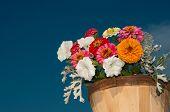 Colorful flowers in wooden bucket against deep blue skies poster