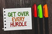 Handwriting text Get Over Every Hurdle. Concept meaning Overcome any obstacle problem trouble adversities Colorful words with white page red green orange pen on blackish wooden desk. poster