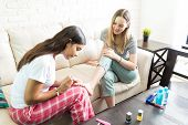 Young woman applying nailpolish on friend's toenails during sleepover party at home poster