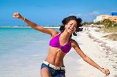 Beautiful caribbean woman dancing on the tropical beach poster