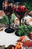 Wine in glasses ,red berries,bumps, candles and autumn branches on wooden table. Autumn or Winter concept. poster