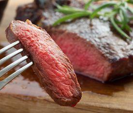 Medium Roast Rib-eye Steak On Wooden Plate With Pepper And Salt And Slice Of Steak On Fork