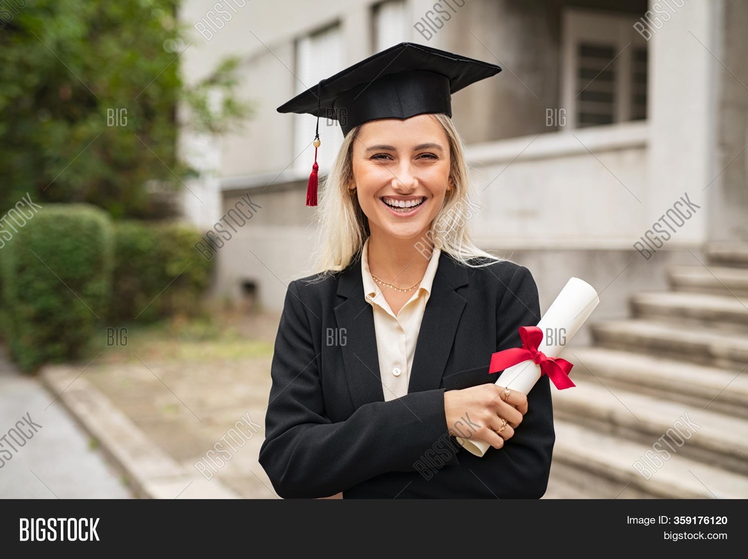 Portrait of satisfied student with mortar board holding diploma degree. Happy young graduate woman standing and looking at camera. Beautiful proud girl smiling in graduation cap with certificate.