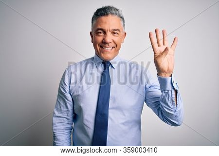 Middle age handsome grey-haired business man wearing elegant shirt and tie showing and pointing up with fingers number four while smiling confident and happy.