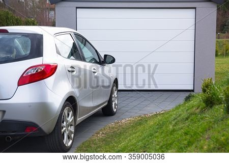 Free-standing garage in the garden with a car parked in front of the gate