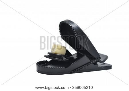 Black Plastic Mousetrap With Cheese On A White Background. The Concept Of Cheating And Bait
