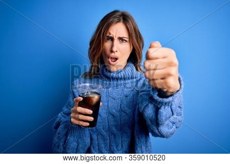 Young beautiful brunette woman drinking glass with cola refreshment over blue background annoyed and frustrated shouting with anger, crazy and yelling with raised hand, anger concept
