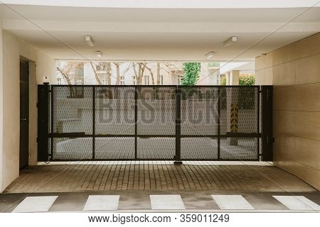 Metalic Black Moving Gate In A Building Gateway, Safe Entrance. No One In The Yard.