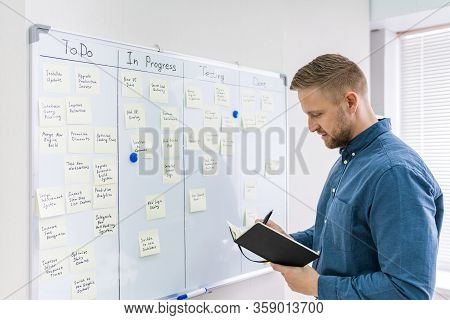Side View Of Businessman Writing On Sticky Notes Attached To White Board In Office