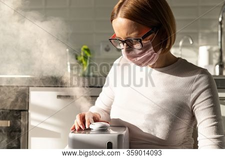 Woman In Face Protective Mask Holding In Her Hands Working Aroma Oil Humidifier In Sunny Room. Humid