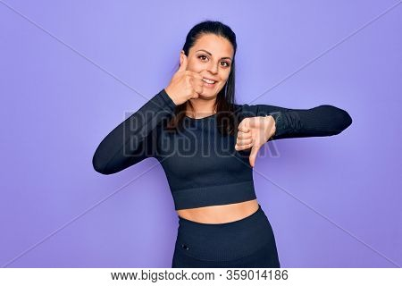 Young beautiful brunette sporty woman wearing casual sportswear over purple background Doing thumbs up and down, disagreement and agreement expression. Crazy conflict