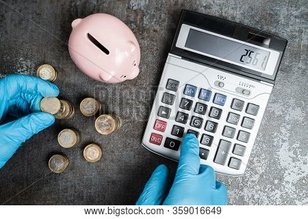 Accountant In Gloves Calculating Piggybank Money Budget During Coronavirus Pandemic