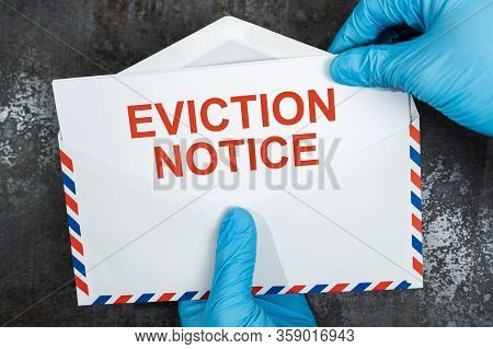 Person Holding Eviction Notice In Envelope