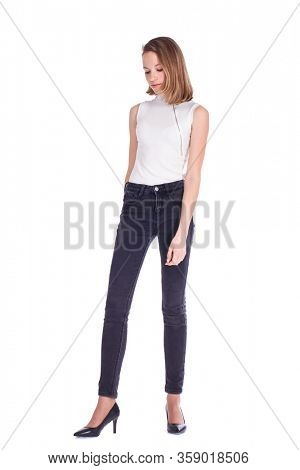 Full body portrait of a young beautiful blonde model in black jeans, isolated on white background