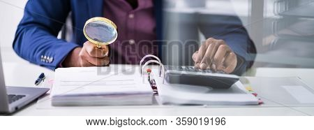 Closeup Of Auditor Scrutinizing Financial Documents At Desk In Office