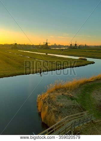 Romantic Dutch Countryside Amidst Extensive Grassy Meadows And Canals Whose Water Reflects The Sunse