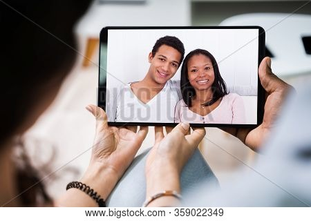 High Angle View Of Young Couple Using Digital Tablet Together At Home