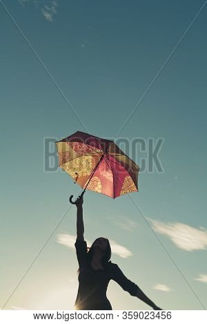 Girl Silhouette Against The Sky Stretches Upwards With A Hand In Which Holds An Umbrella