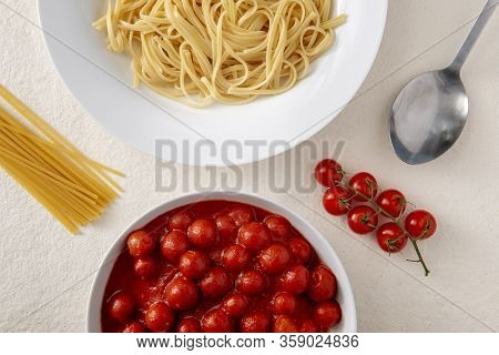 Overhead View Of A Plate Of Pasta Or Spaghetti And A Bowl Of Tomato Sauce Surrounded By Fresh Tomato