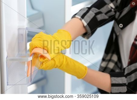 Woman In Rubber Gloves Cleaning Refrigerator, Closeup