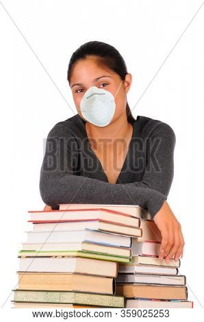 Student wearing protective face mask leaning on stacks of books, ready to be home schooled. Vertical format isolated on white.
