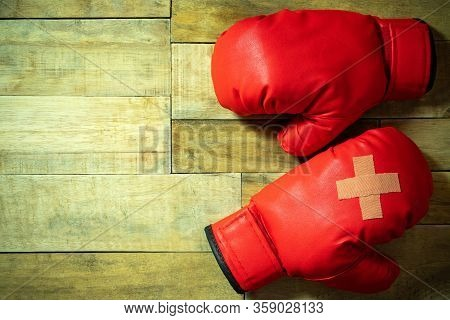 Red Boxing Gloves Placed On Wooden Floor At The Gym. Adhesive Plaster Across Each Other On Boxing Gl