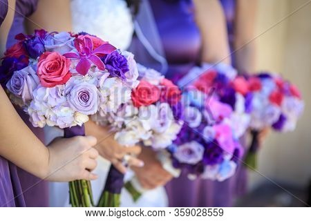 Lavendar, Pink And White Roses And Flower Being Held By Bridesmaid Standing In A Line