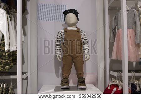 Baby Boy Mannequin In Bandana, Brown Overalls, Striped Shirt On The Background Of A Childrens Clothi