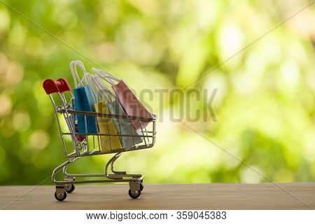 Online Shopping, E-commerce Concept: Paper Shopping Bags In A Trolley Or Shopping Cart  In The Natur