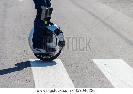 Electric Unicycle. Man Rides On Mono Wheel On Zebra Crossing