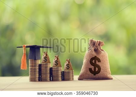 Black Graduation Cap, Hat And Us Dollar Bag On Rows Of Rising Coins,  On A Table. Education Funding,