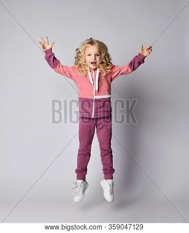 Playful Frolic Screaming Kid Girl In Stylish Modern Pink Gray Sportswear Hoodie And Pants Jumps High