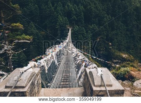 Suspension Bridge Decorated With Multicolored Tibetan Prayer Flags Hinged Over Gorge. Everest Base C