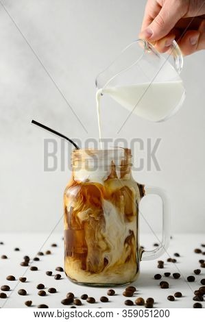 Milk Is Poured Into A Jar Of Iced Coffee On A White Background. Male Hand Pours Cream Into Coffee Wi