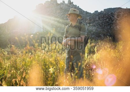 Mature Caucasian Male Hiking In Wilderness With Rucksack And Walking Stick With Sunflare Behind