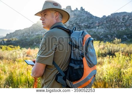Mature Caucasian Male Using Technology To Navigate Hiking In Wilderness With Rucksack And Walking St