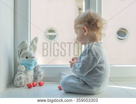 Easter 2020 Concept With Child In Home Quarantine Playing At The Window With His Sick Plush Bunny We