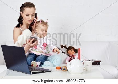 Small child and busy young woman with notebook and phone sit on the sofa in the room. Mother and baby. Isolation period, quarantine, social distancing. Remote work