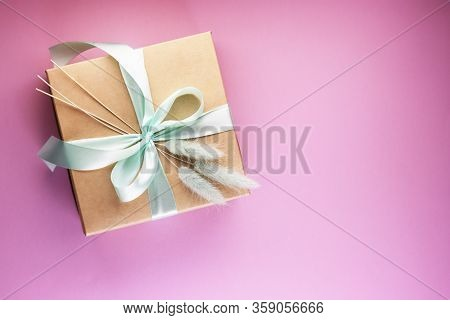A Gift Box And A Flower On The Pink Table On Top. A Box Of Paper With A Blue Bow. Flat Recumbent Sty