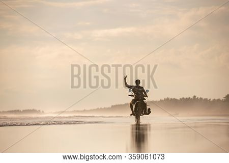 Surfer Rides On Motorbike With Surfboard At Sunset Ocean Beach. Bali Island, Indonesia