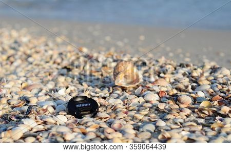 Kyiv, Ukraine - March, 30, 2020: Nikon Snap-on Front Lens Cap Is Lying On The Seashore Sorrounded Wi