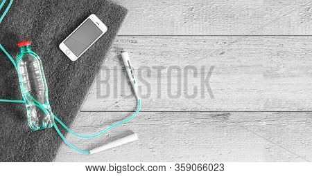 Workout at home during the isolation period yoga mat and jump rope. Fitness with skipping rope, smartphone with a stopwatch or workout plan next to a water bottle. Top view with copy space for text.