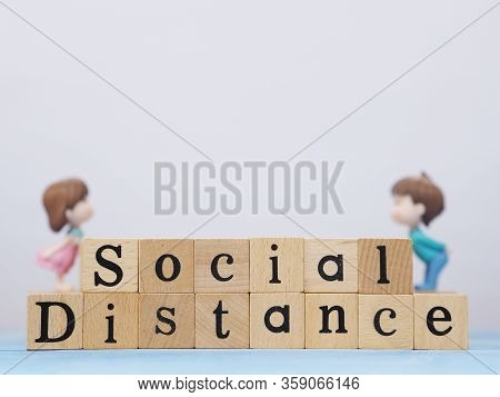 Top View Of Wooden Block With Word Social Distance And Blurry Couple Toy Kissing On Blue Wood Textur