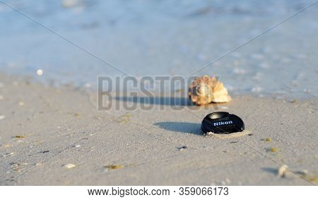 Kyiv, Ukraine - March, 18, 2020: Nikon Replacement Lens Cap On The Seashore, Among Golden Sand, Blue