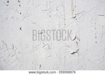 Background Image Of A White Wall. The White Paint Is Cracked. Old Concrete Wall In The Cracks. Textu