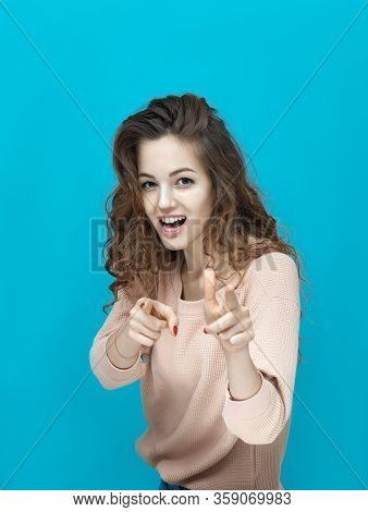 Portrait Of A Young Beautiful Woman Wearing Sweatshirt Points And Looking At You Isolated Over Blue