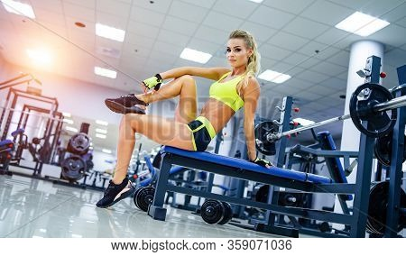 Blonde Sexy Fitness Woman In Sport Wear. Fitness Model With Perfect Body In Gym. Posing Before Train