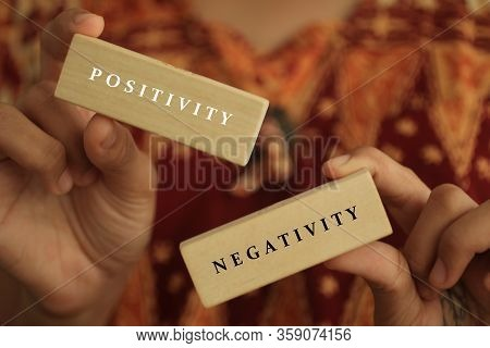 Young Woman Holding Antonym Word Sign Of Positivity And Negativity. Two Wooden Blocks In Hands With